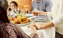 photograph of family holding hands around dinner table